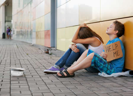beggars: Homeless teenage boy and girl begging in street (The production scene; problem-free children play a role of beggars)