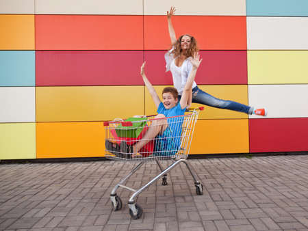 boy and girl  with shopping trolley full of purchases in the street Stock Photo - 18817044