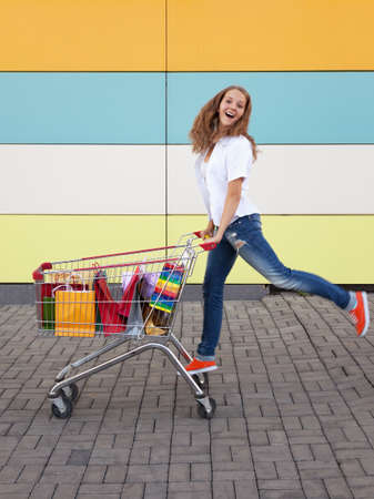 The happy girl the teenager joyfully jumps near to the cart full of purchases photo