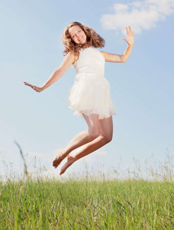 The girl jumps on a green grass Stock Photo