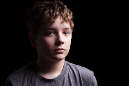 ni�os tristes: Retrato muchacho adolescente triste sobre un fondo negro