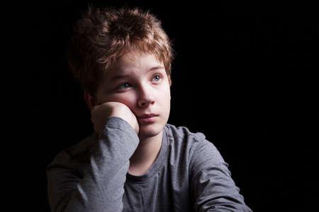 Portrait sad teenage boy on a black background photo