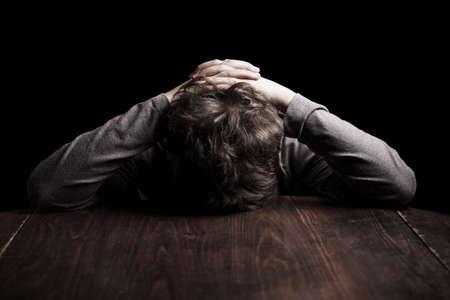 behavior: Retrato muchacho adolescente triste sobre un fondo negro