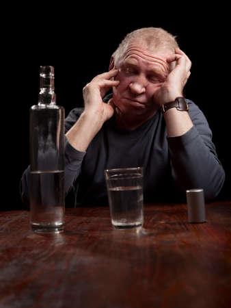 irresponsible: portrait of alcoholic senior man on a black background