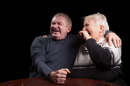 A loving, handsome senior couple on a black background.  photo