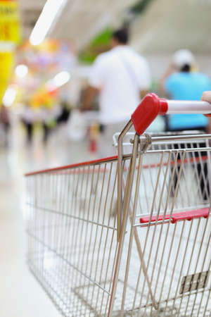 woman shopping cart: Female hand and shopping trolleys