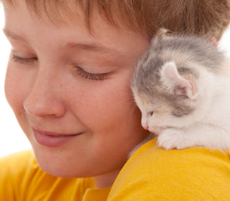 Kitten sleeps on a shoulder of the boy, a close-up
