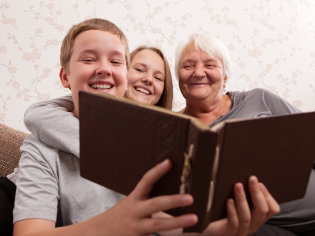 recollection: Senior woman and its grandsons together examine an album with photos Stock Photo
