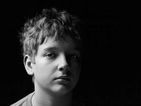 wistful: Portrait sad teenage boy on a black background