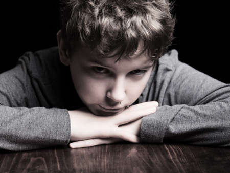 Portrait sad teenage boy on a black background photo