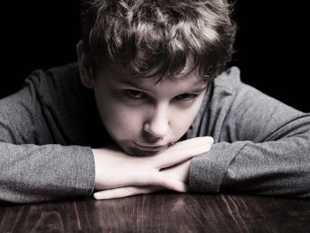 wistful: Portrait sad teenage boy on a black background