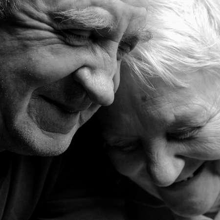 radost: Milující, hezký starší pár na černém pozadí.