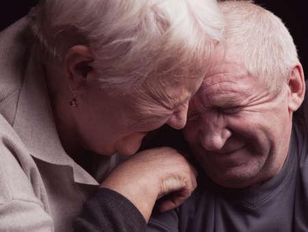 genegenheid: Een liefdevolle, handsome senior paar op een zwarte achtergrond.