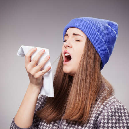 öksürük: Bir grip ile hasta genç kadın, gri üzerinde hapşırma çekim Stok Fotoğraf