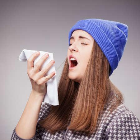 tos: Mujer joven enferma con una gripe, estornudos primer sobre gris Foto de archivo
