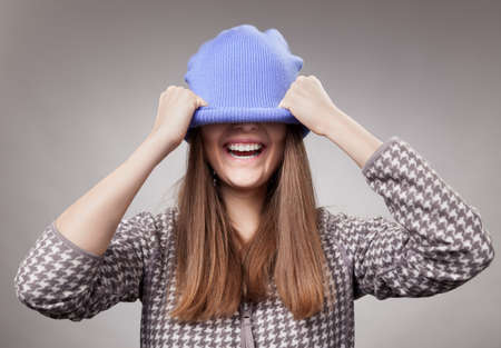 Portrait of playful woman in knitted winter cap smiling  Stock Photo