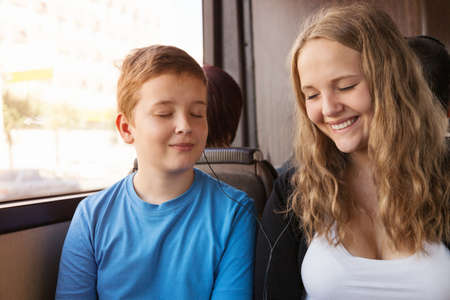 the occupant: The girl and the boy go in the bus and listen to music in phone