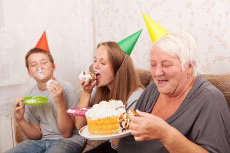 boy and teenage girl on birthday eat a cake photo