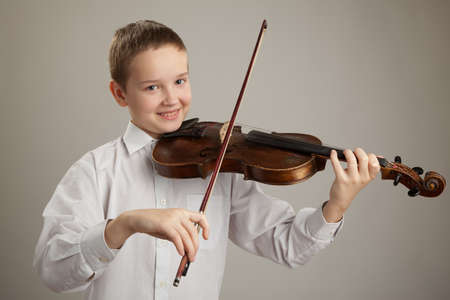 Teenager playing the violin, gray background photo