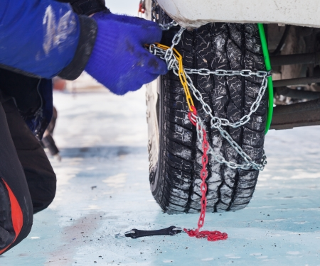 Man installing snow chain on car Stock Photo