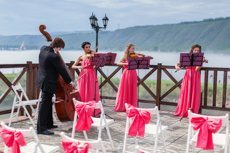 Quartet of classical musicians playing at a wedding outdoors near the river