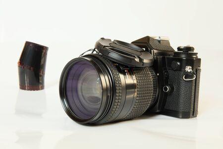 Film camera in black and color negative film on a light background closeu