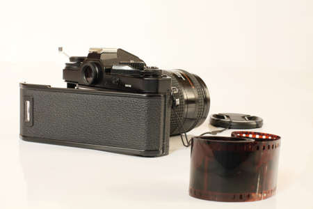 Film Camera Black with open back cover and color negative film on a light background closeup