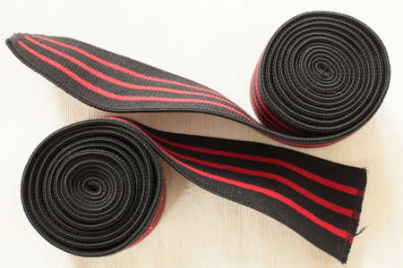 Bandages are black and red for doing powerlifting on a light background closeup