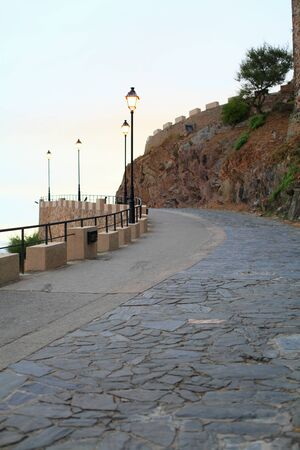 Paved with stone expensive, leading to an ancient castle in the background of the Mediterranean sea in Catalonia
