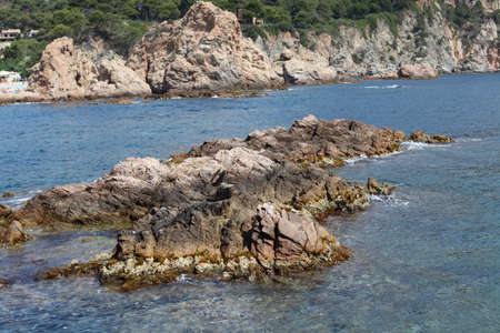 Reefs or a small island near the coast of the Mediterranean sea close up against the background of the calm sea