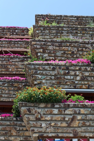 The balconies of the residential houses, decorated with flowers on the background of blue sky