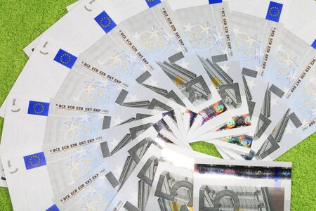 Banknotes five euros are a fan closeup on a green background