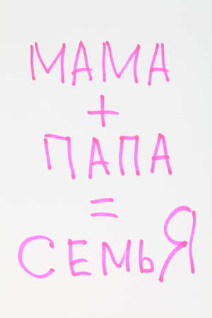 The expression  Mom   dad = family  is written bright pink marker on a white sheet of paper