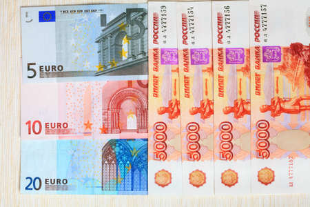 Photo bills of the Russian Federation and the European Union closeup on a light background  Stock Photo