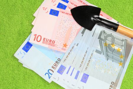 Photo of banknotes of the European Union and shovels closeup on a green background