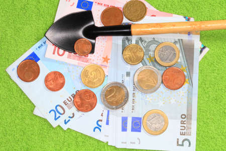 Coins and banknotes of the European Union and a shovel closeup on a green background  Stock Photo