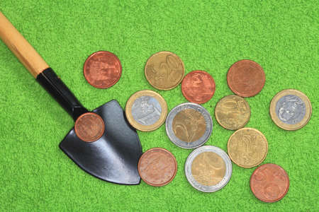 Coins of the European Union and the United States on a shovel on the green background of close-UPS  Stock Photo