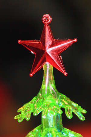Photo red five-pointed stars close up on the green artificial Christmas tree  Stock Photo