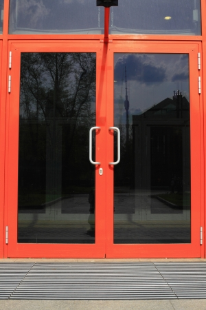 glass house: The door, tinted glass with a bright pink frame in the office building  Stock Photo
