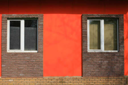 Two Windows in the brick wall of the office building of dark brick pink and bright wall  photo