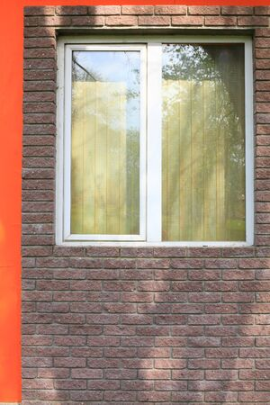 The picture window in the wall of the building of dark brick close-up on a Sunny day