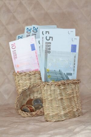 Notes in denominations of 5, 10 and 20 euros a close-up in a basket on a light background. photo