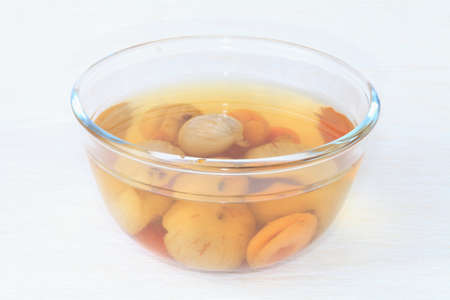 Compote of figs, apricot, Cornel in a glass transparent bowl closeup on a light background  photo