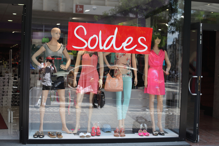 Advertising inscription  sale  is a closeup of the glass window of the store, which sells women Editorial