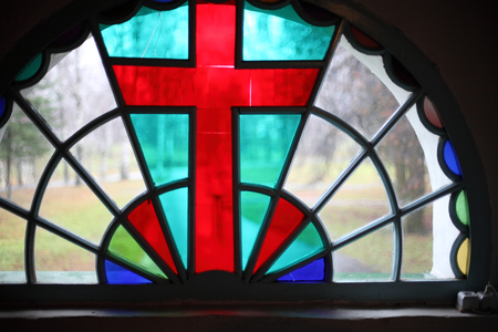 Close-up of colorful stained glass window with a central image of the red cross, illuminated by light passing day. Stock Photo