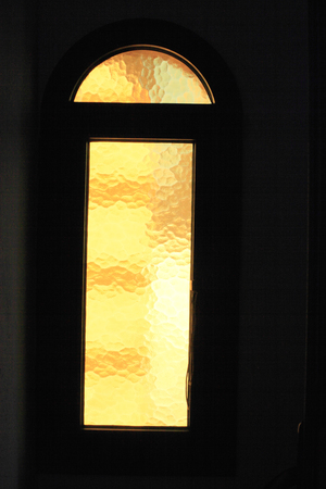 Window with yellow glass closeup in a white wall.