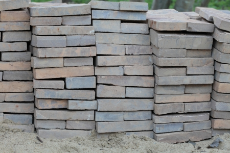 Tile construction close-up, neatly folded rows of dark colour on a light sand  Stock Photo