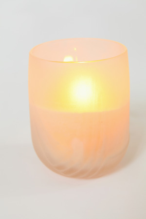 Candle burning in the bright decorative glass closeup on a white background  Stock Photo