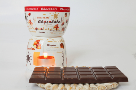 Chocolate fondue tiles and dark chocolate closeup on a light background
