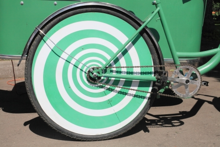 Wheel rear bike green color close-up on the road on a Sunny summer day.